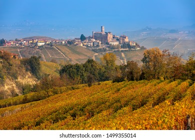 View of beautiful autumnal vineyards and small medieval town on the hill on background in Piedmont, Northern Italy.