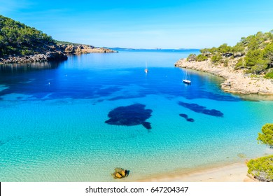 View of beautiful beach in Cala Salada bay famous for its azure crystal clear sea water, Ibiza island, Spain