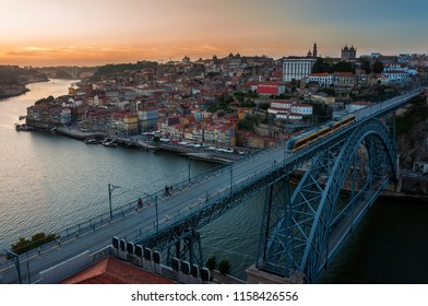 View of the beautiful city of Porto at sunset with the Douro River and the Dom Luis Bridge; Concept for visit Porto and travel in Portugal