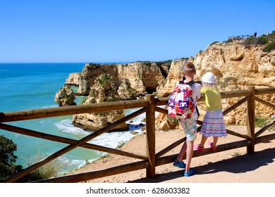 View from the beautiful cliffs above Praia da Marinha beach in south Portugal. Children hiking and enjoying one of the most spectacular places in Lagoa, Algarve region.