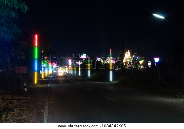 View beautiful decorative lights on the side of a rural road in Thailand at night under a temple festival.