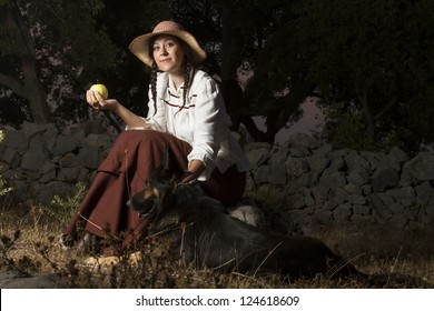 View of a beautiful girl in a classic dress in a countryside set with a dog.