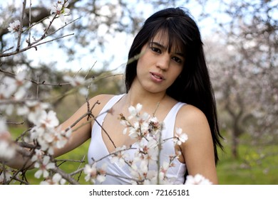 View of a beautiful girl on a white dress on a green grass field next to  a almond tree.