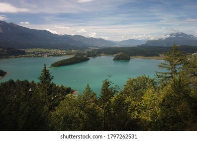 View of a beautiful green lake with an island in the middle situated between mountains and large forest areas