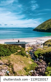 View of beautiful Keem Bay on Achill Island along the Wild Atlantic Way in County Mayo, Ireland. Taken on a sunny day in summer, showing the beach and structures.