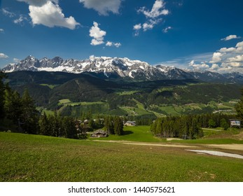 View of beautiful landscape in the Alps with fresh green meadow and Dachstein massif in the background