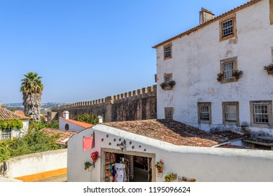 View of the beautiful medieval historic center village of Obidos and Castle of Obidos. Wonderful romantic afternoon landscape at sunny weather. District of Leiria, in the centre of Portugal.