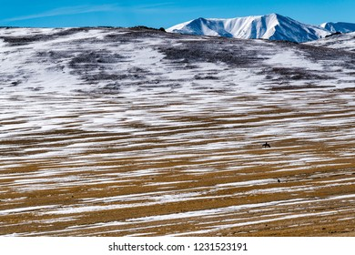View of beautiful mountain with the horsemen at the strips of white snow on the dark brown ground in Mongolia