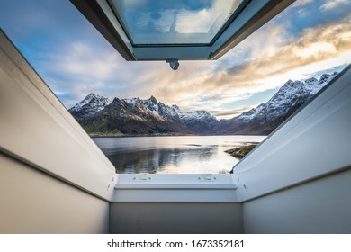 View of beautiful mountains near sunset with clouds from an open window on a roof