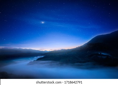 View of beautiful night sky with stars in foggy mountain valley. Scenic landscape of misty hills under blue starry sky. Concept of astrology and magical nighttime.