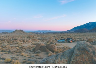 View of beautiful pink & purple sunset over rocky desert while camping/overlanding with off roading vehicle and trailer