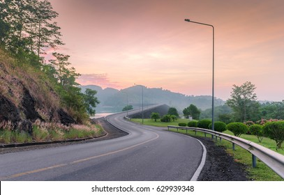 view of beautiful S curved road on the dam with the sunrise behind moutain and sweet twilight sky