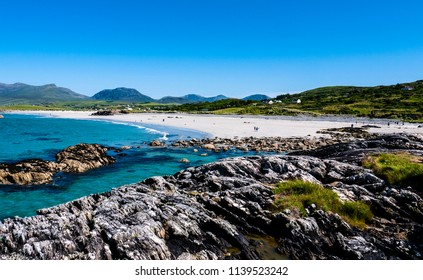 View of a beautiful sandy beach from the rocks on a sunny day with clear blue ocean and blue skies. Taken in summer in Renvylle, along the Wild Atlantic Way, Ireland.