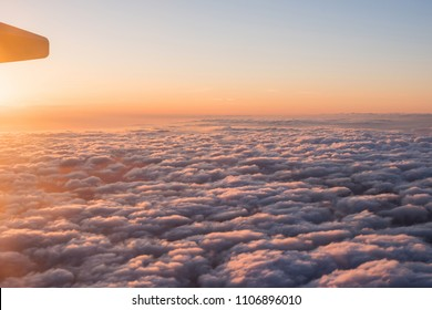 View of the beautiful sky and clouds from the window of the airplane. Sunset sky from the window of the airplane. Wing of an airplane against a beautiful sunset sky.