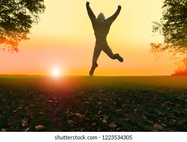 view of the beautiful sunrise/sunset and a cheerful jumping young person
