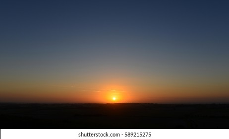 View of a Beautiful Sunset and Clear Sky over a Silhouetted Land Horizon