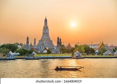 View of beautiful Temple of Dawn or Wat Arun and boats on Chao Phraya River at sunset with shining sun. Bangkok, Thailand