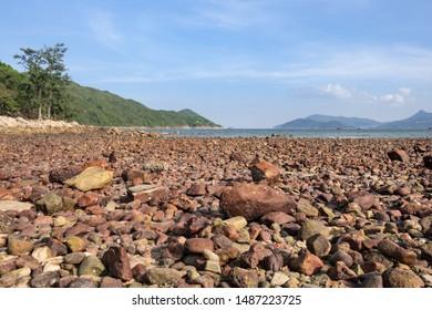 View of beautiful volcanic rock beach of Sharp island or Kiu Tsui Chu with blue sky, Hong Kong.