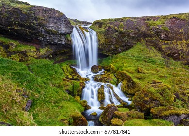 View of beautiful waterfall among the grass and stones in Iceland