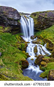 View of beautiful waterfall among the grass and stones in Iceland. Vertical view.