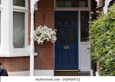 View of Beautiful White Petunia Flower in Hanging Basket are Next to Blue Front Door of House. Concept: English Garden Style.