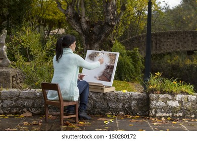 View of a beautiful young woman painting on a urban park.