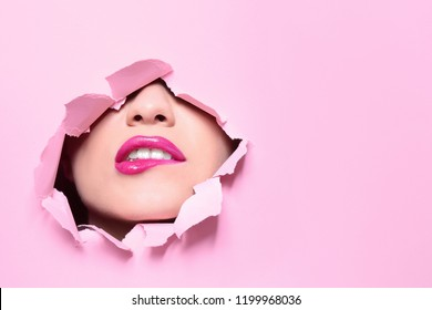 View of beautiful young woman with perfect lips makeup through hole in color paper. Space for text