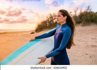 View of beautiful young woman surfer girl in wetsuit with surfboard on a sand beach at sunset or sunrise
