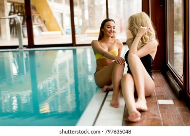 View at beautiful young women relaxing by  spa swimming pool