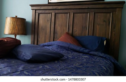 "View of bed covered in brown and blue linen.  Large, dark, wood headboard.   ""Home, sweet home.""  ""There' s no place like home."""