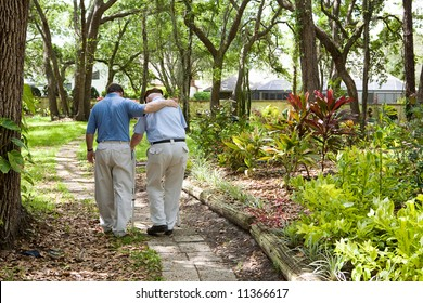 View from behind of an adult son walking with his senior father in the park.