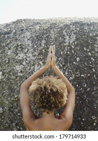View from behind of the bare head and shoulders of a young Asian woman practising yoga meditating with her hands raised above her head against a granite rock