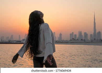 View from behind black woman spreading arms during sunset