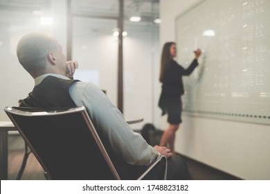 View from behind of a boardroom with a businessman in an office armchair closely observing how his female colleague in a defocused background makes a business presentation using electronic whiteboard