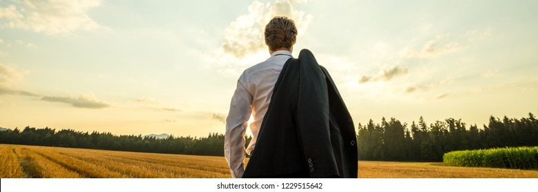 View from behind of a businessman standing in nature under evening sky looking in to the distance with his suit jacket over his shoulder.