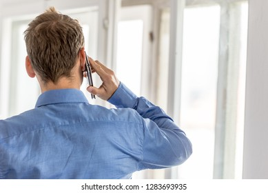 View from behind of a businessman talking on a mobile phone facing the windows in a bright office.