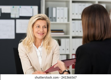 View from behind of a female job applicant handing over her CV to a smiling middle-aged manageress
