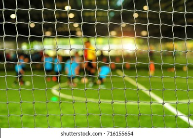 View from behind the goal of soccer field. Blurry scene of football coach and children playing soccer in football field at indoor stadium. Soccer training for kids.