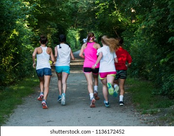 The view from behind of a group of five girls running down a dirt path that is lined by green trees.