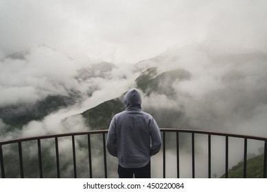 View from behind of a man standing at view point looking to beautiful landscape with foggy mountains in the distance