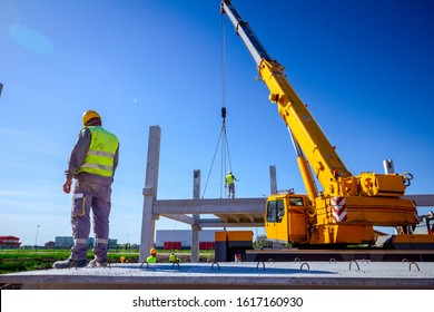 View from behind on construction worker with safety vest and yellow helmet overseeing mobile crane to manage concrete joist for assembly huge construction.
