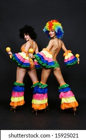 view from behind on two attractive dancers with maraca against dark background