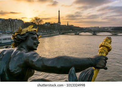 View from behind of one of the Nymphs of the Seine ornamenting the downstream keystone of the Pont Alexandre III, with the Pont des Invalides and the Eiffel tower in the background at sunset.