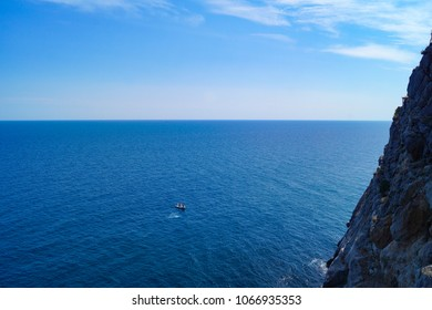 View from behind a rock on the blue sea and the blue sky, separated by the horizon. Black Sea, Swallow's Nest, Crimea