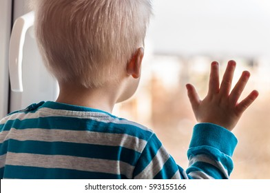 View from behind of small sad two years old boy standing by the window and waiting for something