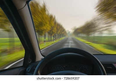 A view from behind the steering wheel of a car going through the fall