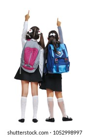 View from behind of two schoolgirls pointing to the copy space area
