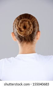 View from behind a woman with her brunette hair done in a neat bun on the back of her head against a grey studio background