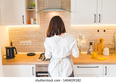 view from behind woman on kitchen cooking housewife