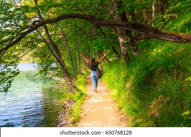 view from behind of a young girl in forest path near a lake in plitvice national park